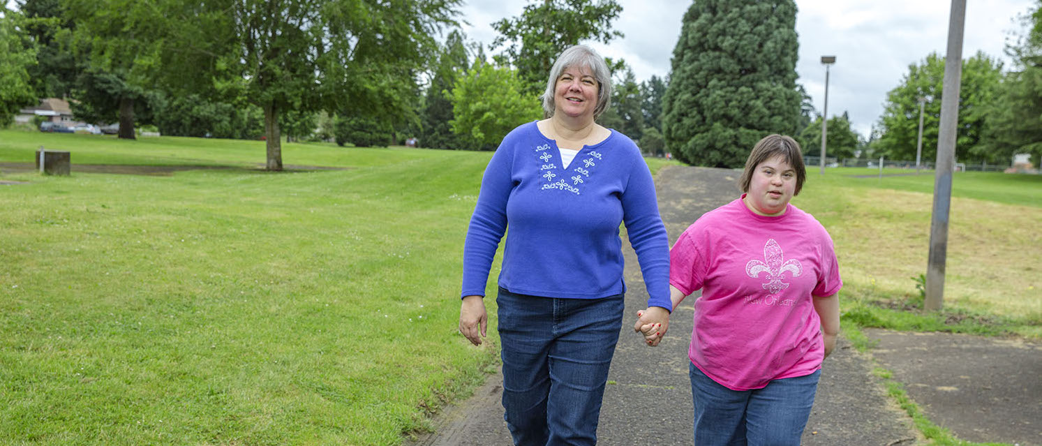 Homecare worker walking and holding hands with her daughter who is also her client