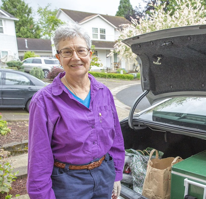 Personal Support Worker unloading groceries from the trunk of her car